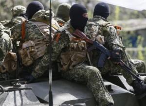 Armed men drive an armoured personnel carrier in Slaviansk
