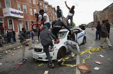 Протестующие уничтожили несколько полицейских машин и подожгли здание. Фото AFP